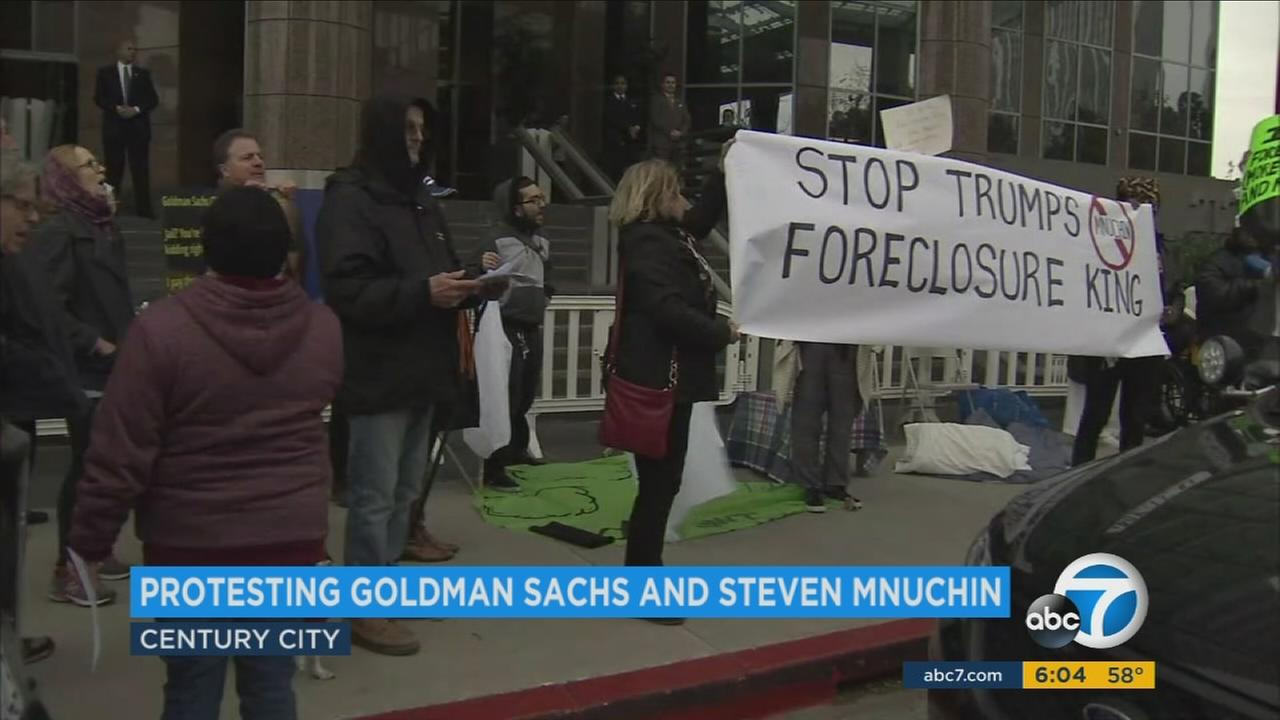 Protesters hold up signs urging Congress to deny Donald Trumps treasury pick Steven Mnuchin from being confirmed.