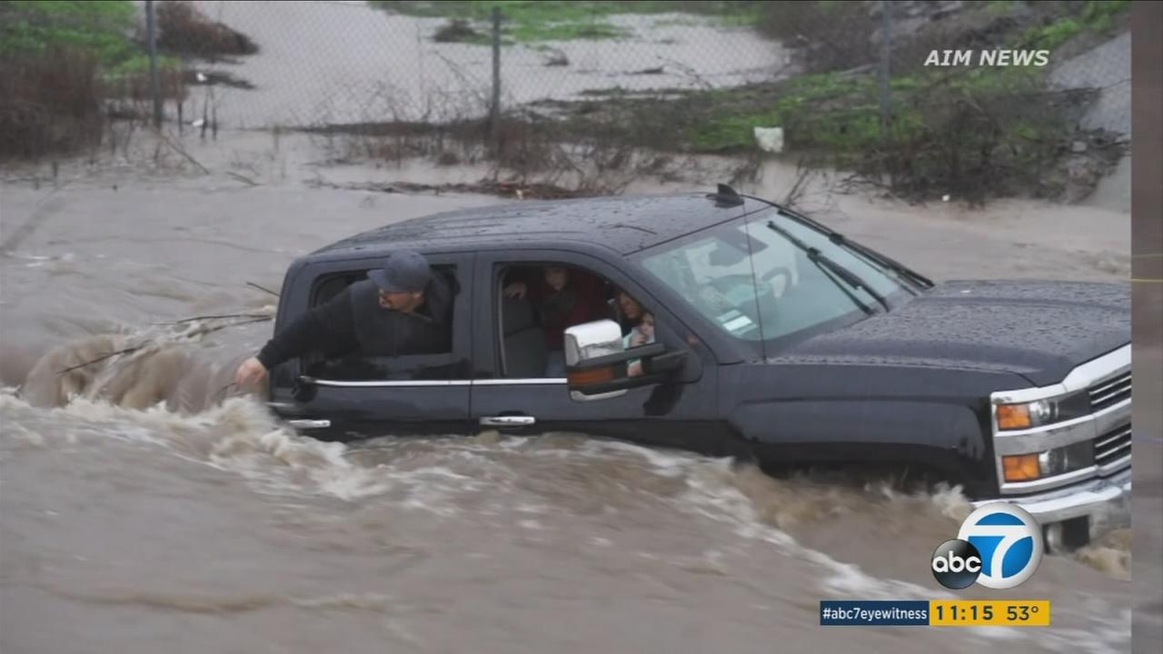 A truck with a family inside is trapped in floodwaters in the Inland Empire on Sunday, Jan. 22, 2017.