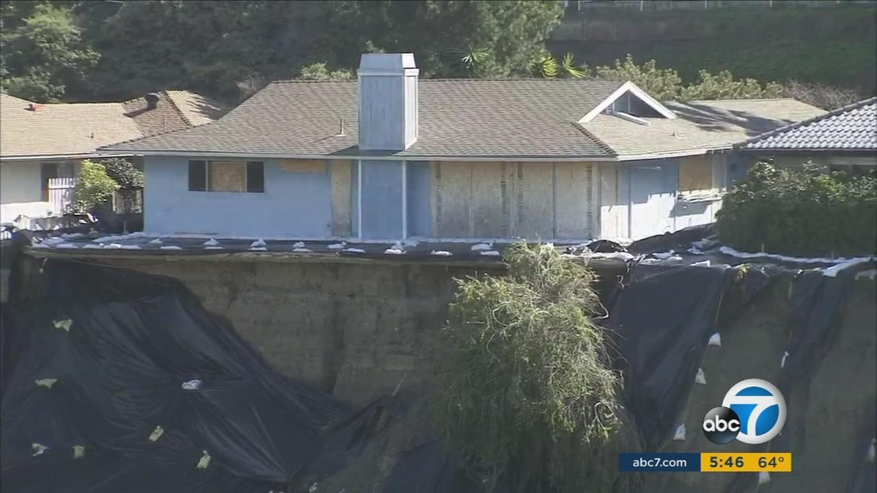 One of the damaged, boarded up homes sits on a small piece of hillside in San Clemente.