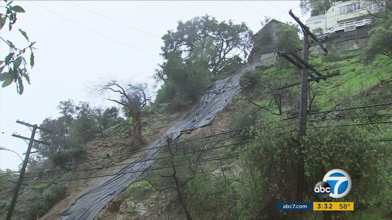 Black tarpaulins cover a rain-soaked hillside in the Hollywood Hills following a landslide near Laurel Canyon Boulevard.
