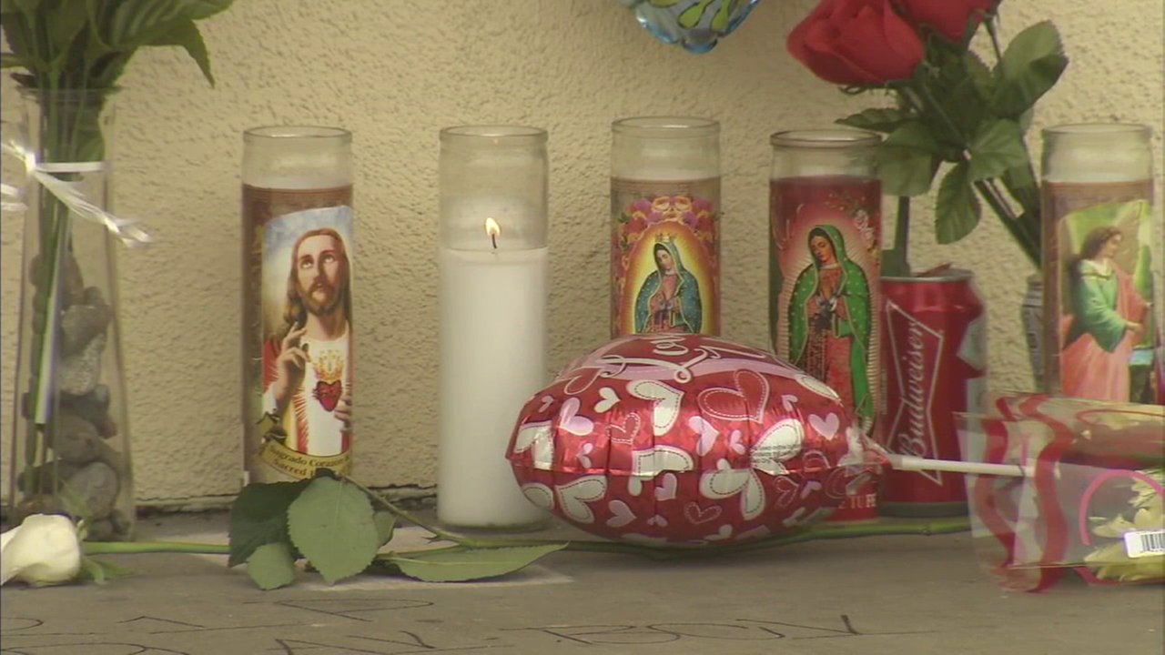 A vigil with religious candles and flowers is shown at a memorial site in Santa Ana where a person was killed in a slew of gang violence within the city.