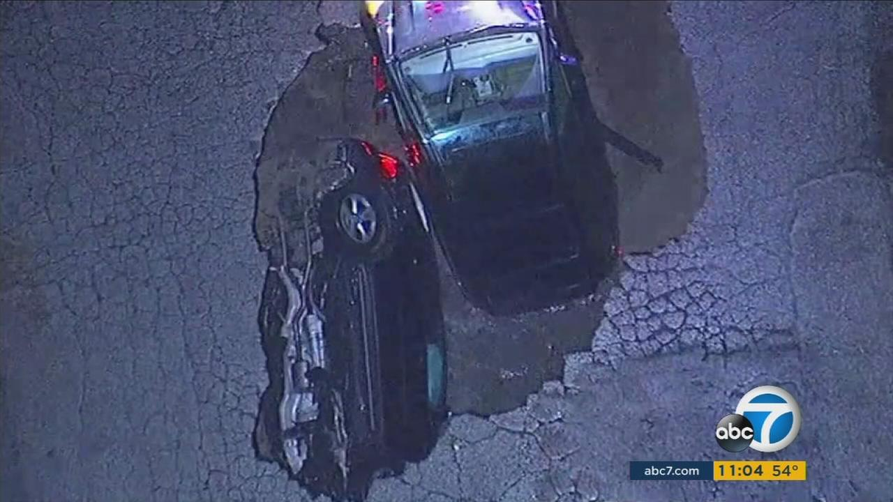 Fire crews pulled a driver out from underground after two cars plunged into a massive sinkhole in Studio City Friday night. The second driver escaped before falling in the hole.