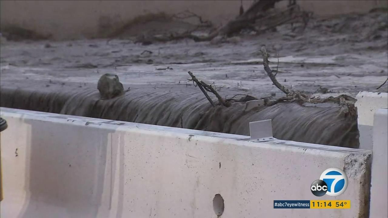 Mud flowed freely down hillsides and streets in burn areas of Duarte, overflowing barriers but for the most part homes had been spared serious damage as of late Friday evening.