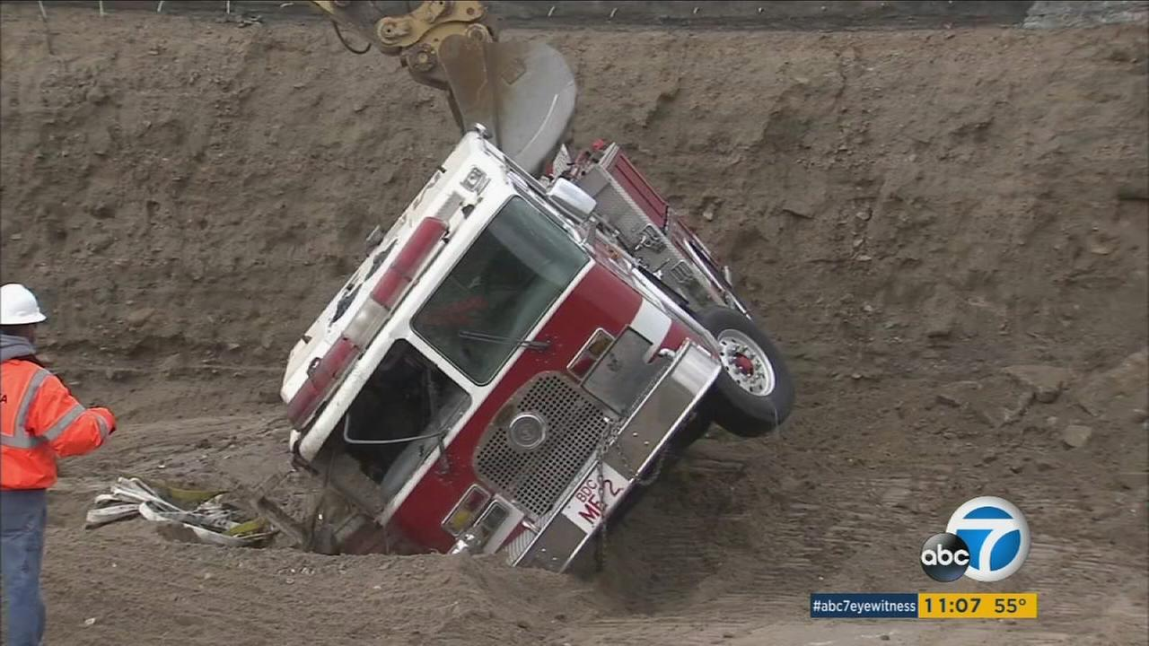 Crews had to dig a fire truck out from heavy mud after it fell over the side of the 15 Freeway in the Cajon Pass.