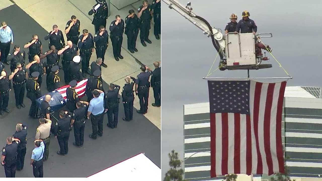 A long line of law enforcement officials salute the flag-draped body of a slain Whittier police officer outside the coroners office in Santa Ana on Monday, Feb. 20, 2017.
