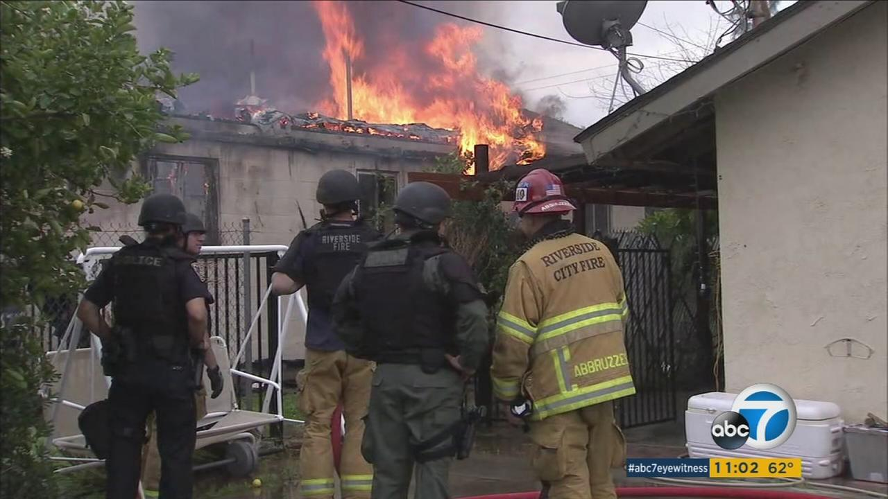 Authorities look over the damage of a fire that erupted inside a home where a suspect who shot at officers may have been inside in Riverside on Tuesday, Feb. 21, 2017.