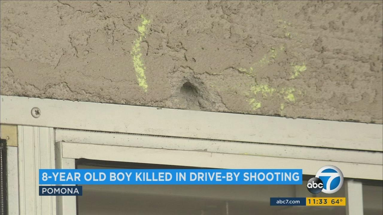 A bullet hole is shown at a Pomona home where a drive-by shooting occurred that left an 8-year-old boy dead.