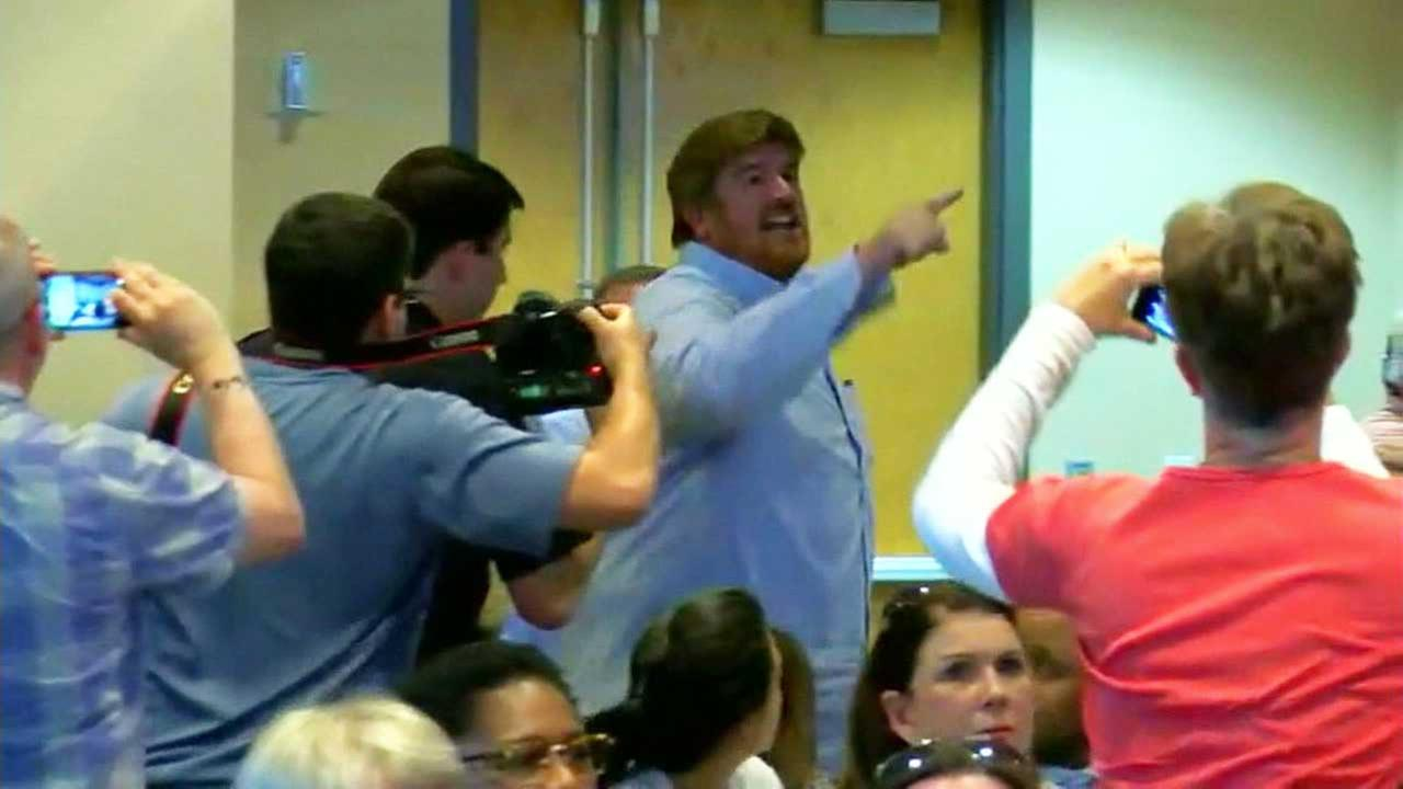 An angry constituent shouts during a town hall meeting.