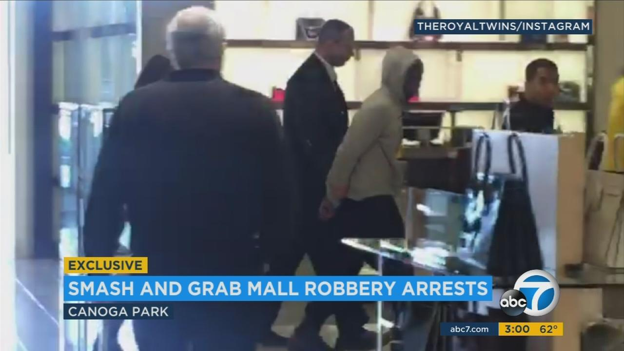 A suspect is taken away by security at Neiman Marcus after a smash-and-grab attempt of high-end purses.