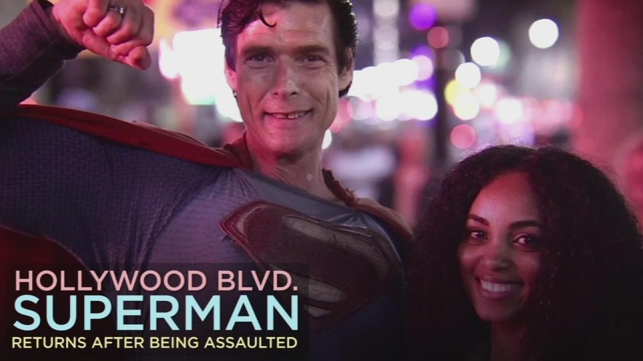 Christopher Lloyd Dennis, known as the Hollywood Boulevard Superman character, is shown in a photo with a tourist.