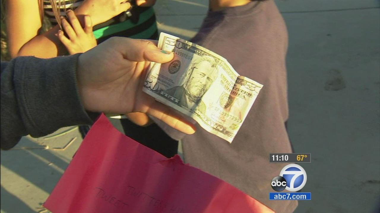 A hand holds up a $50 bill found during the Hidden Cash scavenger hunt at Kenneth Hahn State Recreation Park on Friday, July 11, 2014.