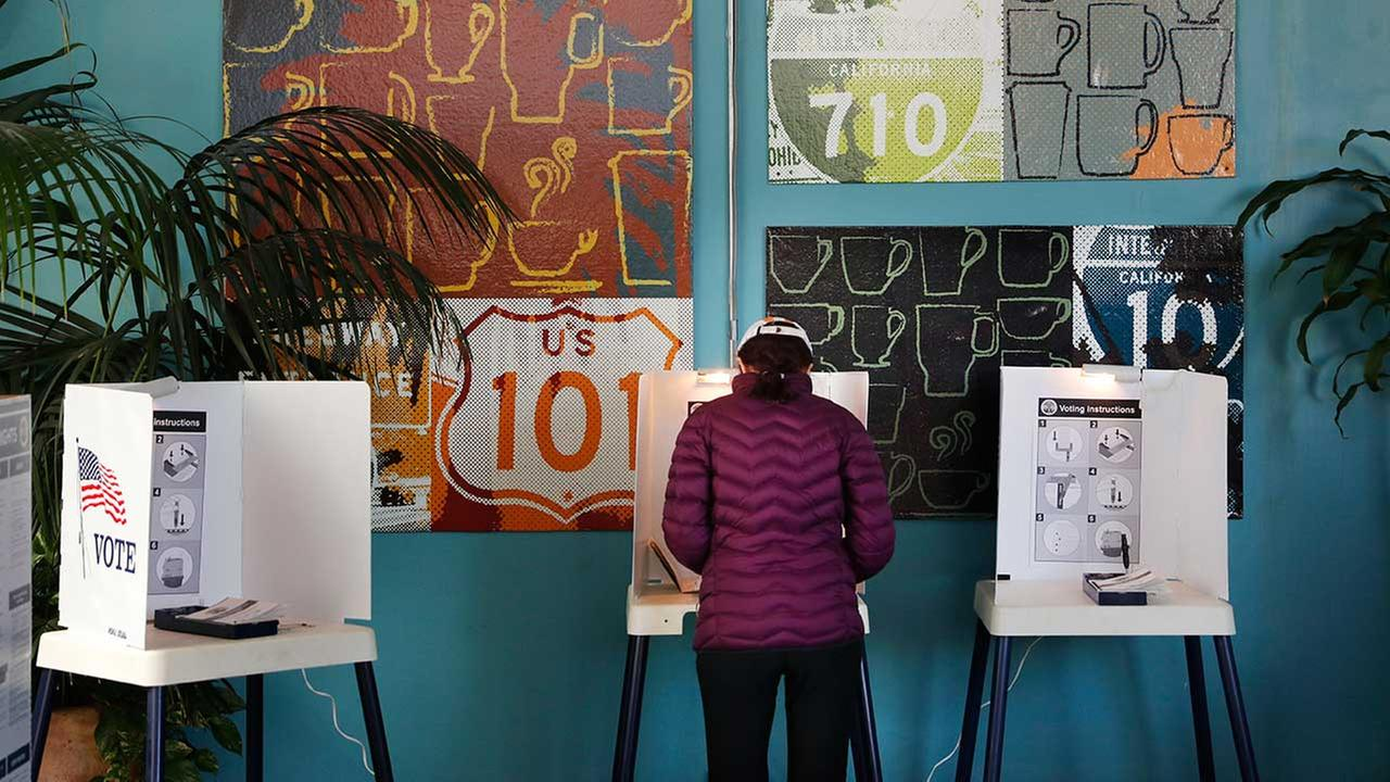 A woman votes at a polling station inside a coffee shop Tuesday, March 7, 2017, in Los Angeles.
