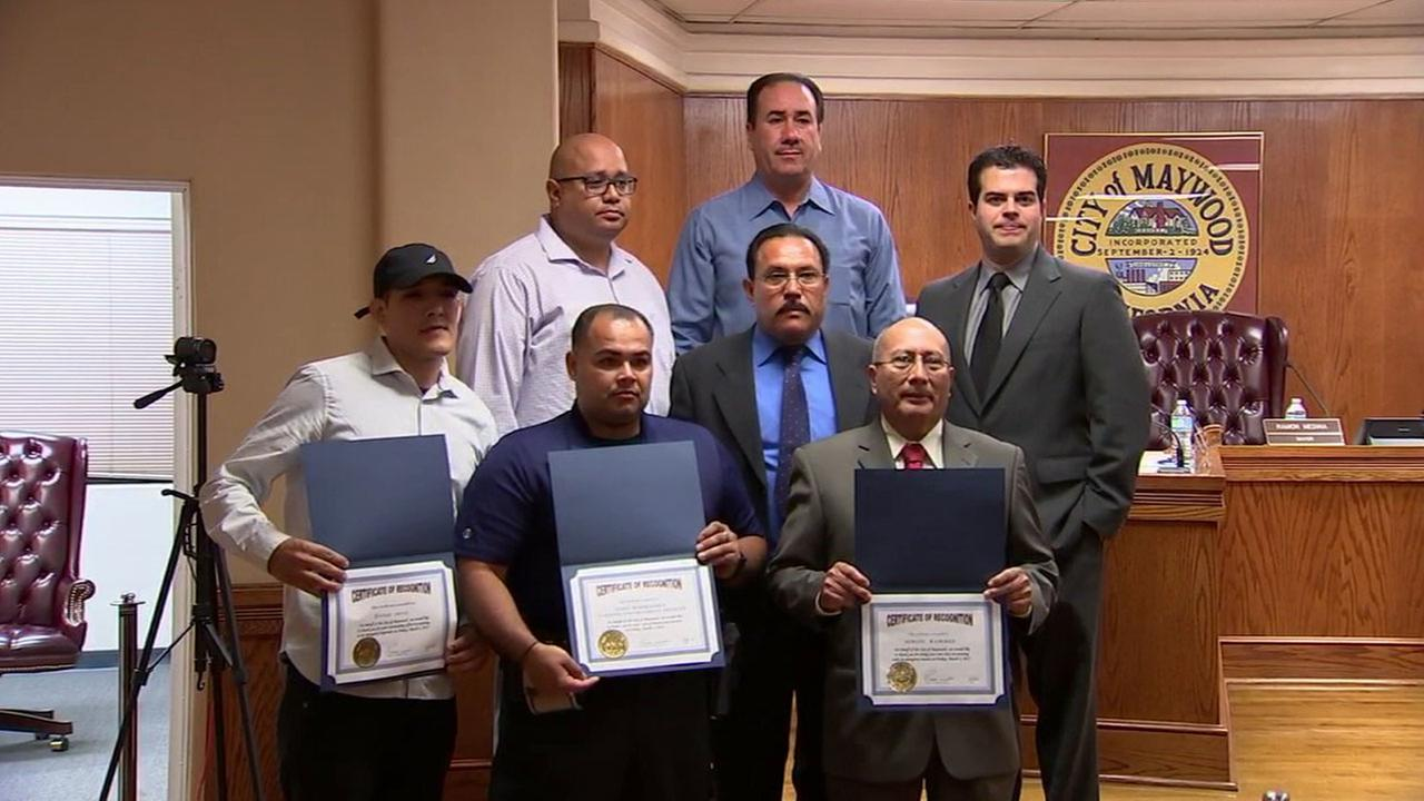 Three men hold up certificates honoring them for their help in catching a suspect who tried to flee the scene of a fatal crash in Maywood.