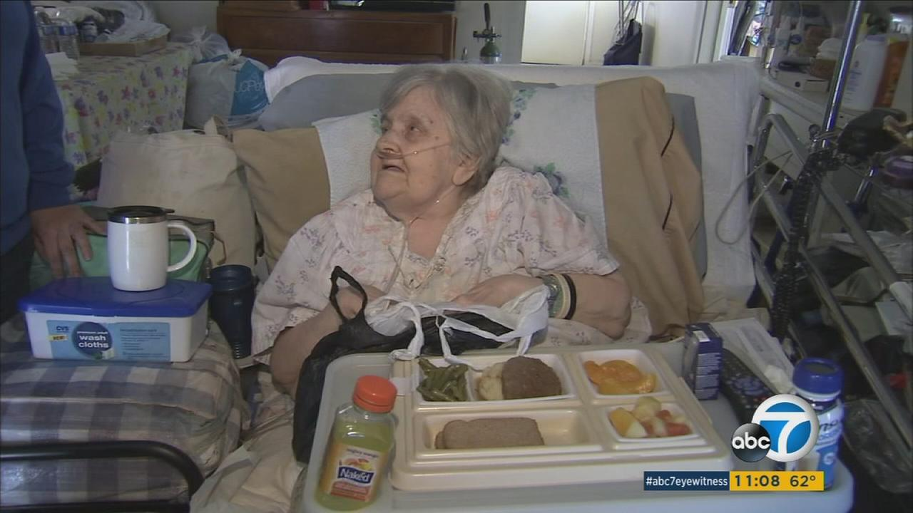 An elderly woman in need receives food from Meals on Wheels.