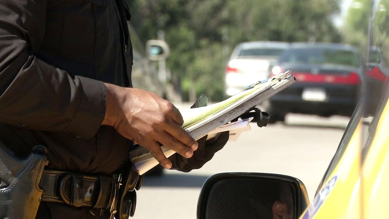 An officer gives a person a ticket after patrolling one of five dangerous intersections in South Los Angeles.