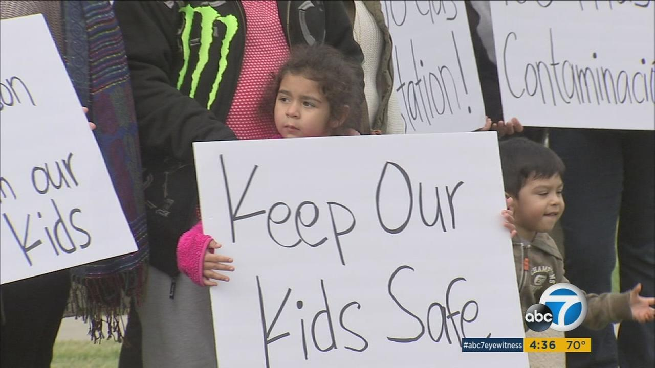 A little girl holds up a protest sign after the Pomona Planning Commission approved the building of a gas station near a school.