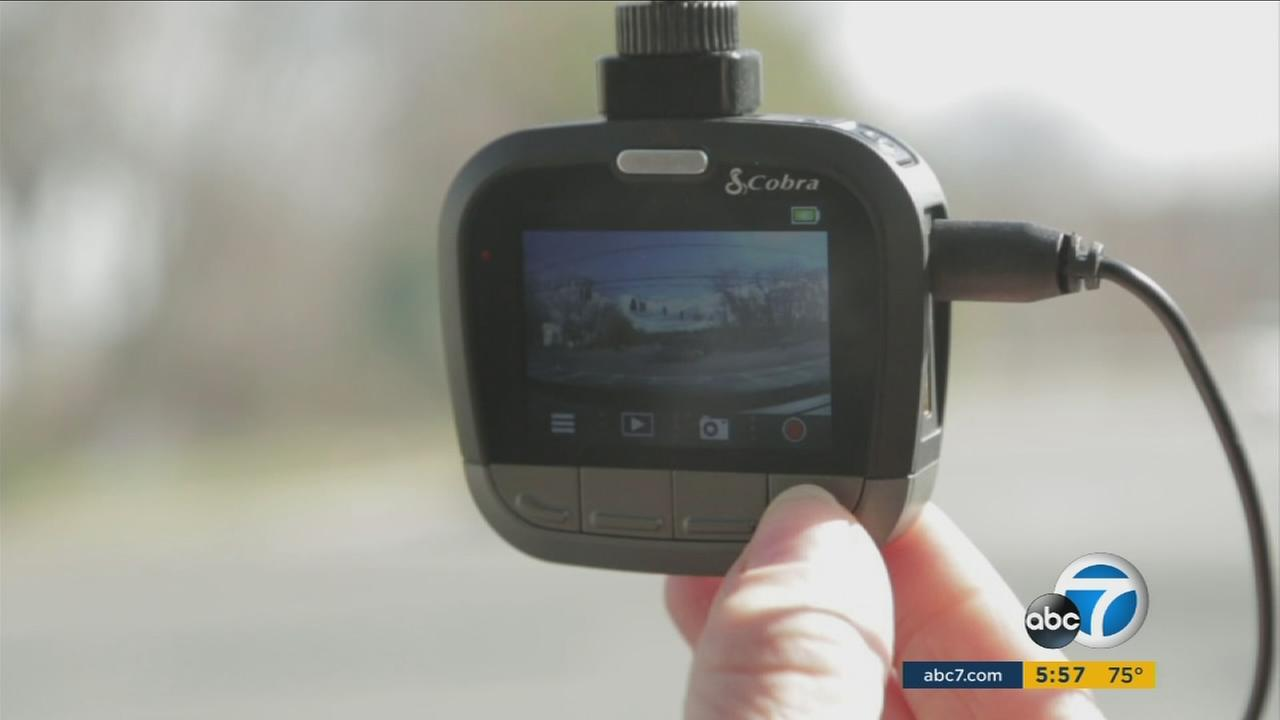 A dashcam is shown inside of a car.