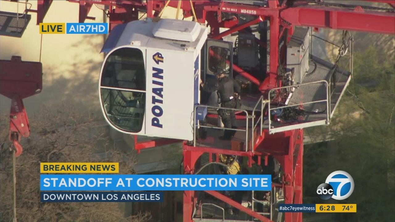 A woman who scaled a tall crane at a construction site in downtown Los Angeles and locked herself inside it exited the cranes cab and was sitting precariously on its platform 150 feet above the ground before rescuers reached her.