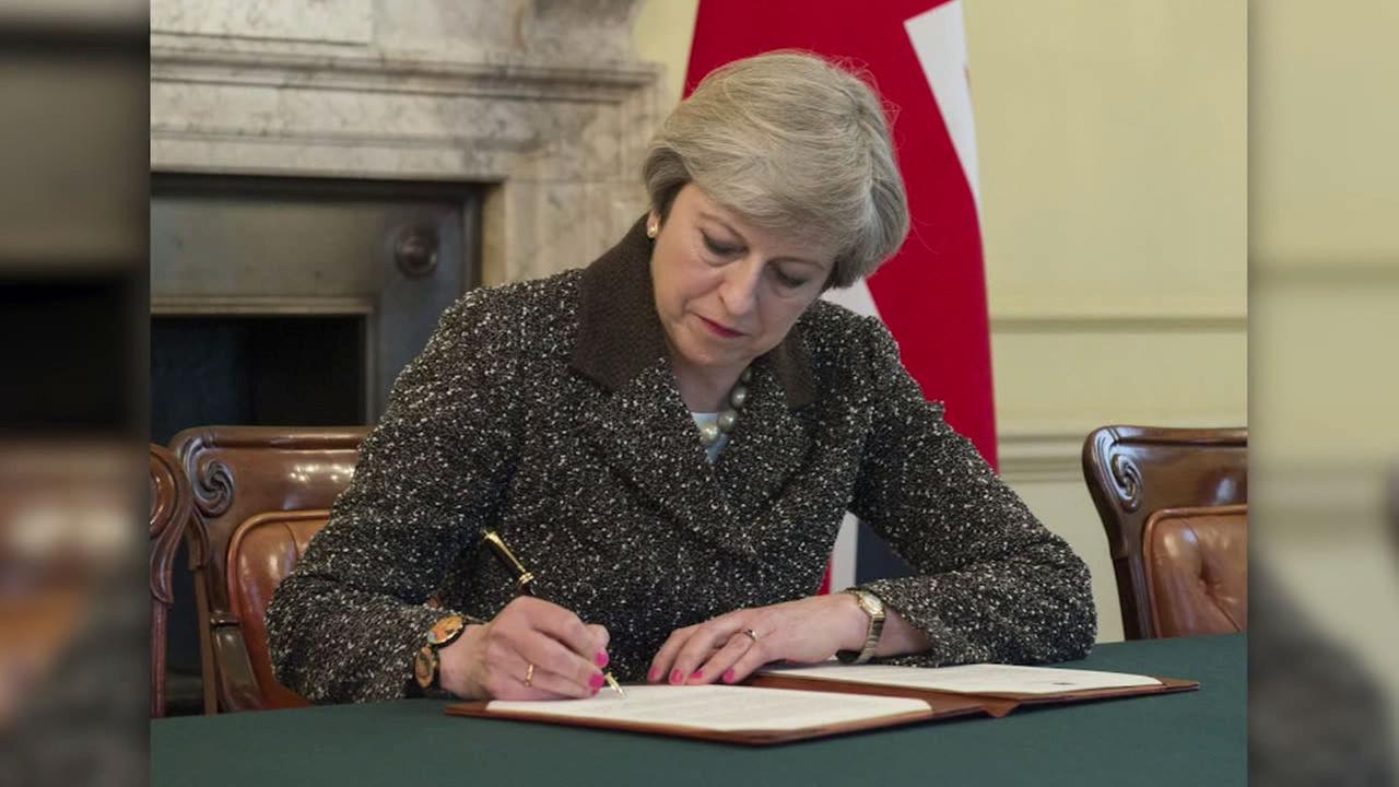 Britains Prime Minister Theresa May signs the official letter to European Council President Donald Tusk on March 28, 2017.