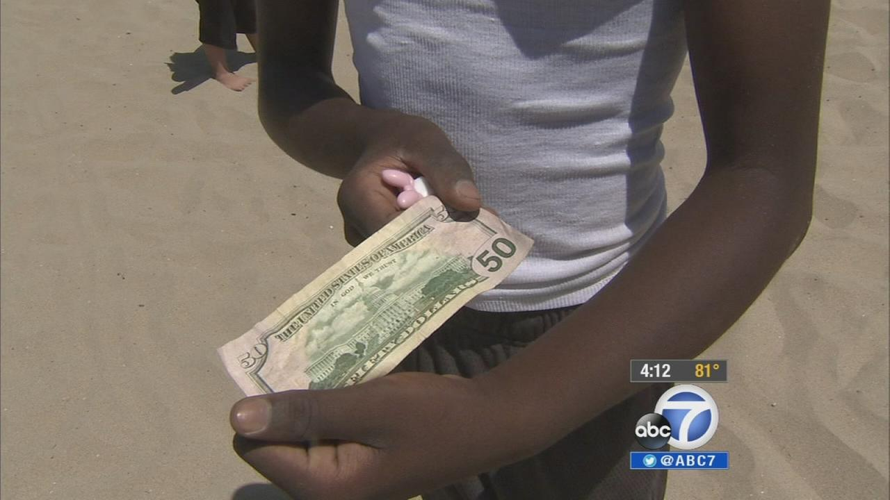 A $50 bill is found in the Hidden Cash hunt at Hermosa Beach on Sunday, July 13, 2014.