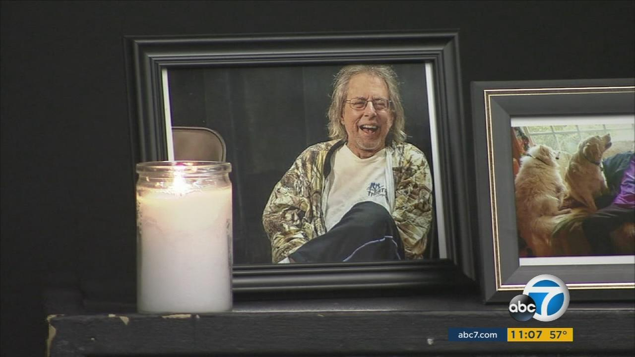 A candle is lit next to a photo of the late Gary Austin, the founder of Los Angeles The Groundlings Theatre.