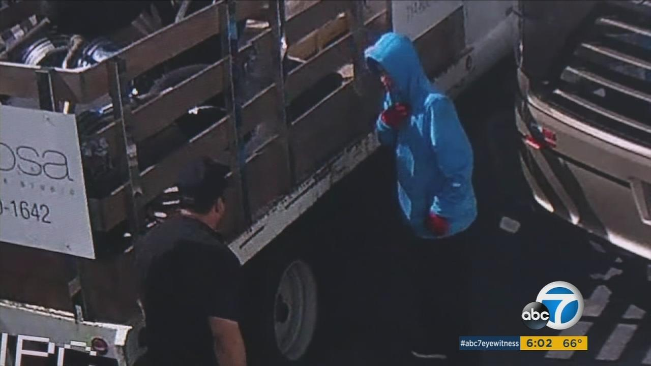 Two suspects who stole a trailer and motor coach from a Santa Ana sports business are shown on surveillance video.