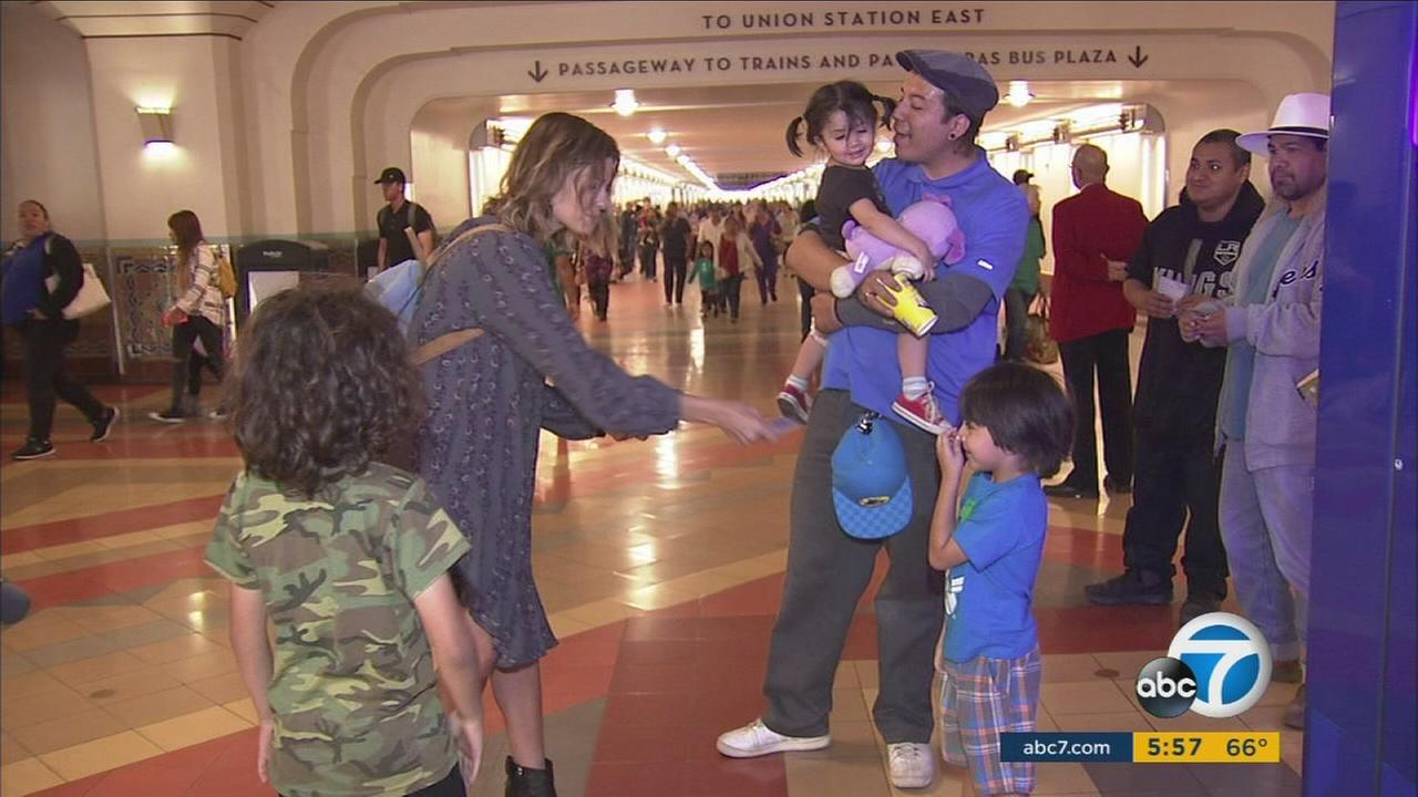 A woman with HELP the 11th gives out a Metro tap card worth $10 to a family.