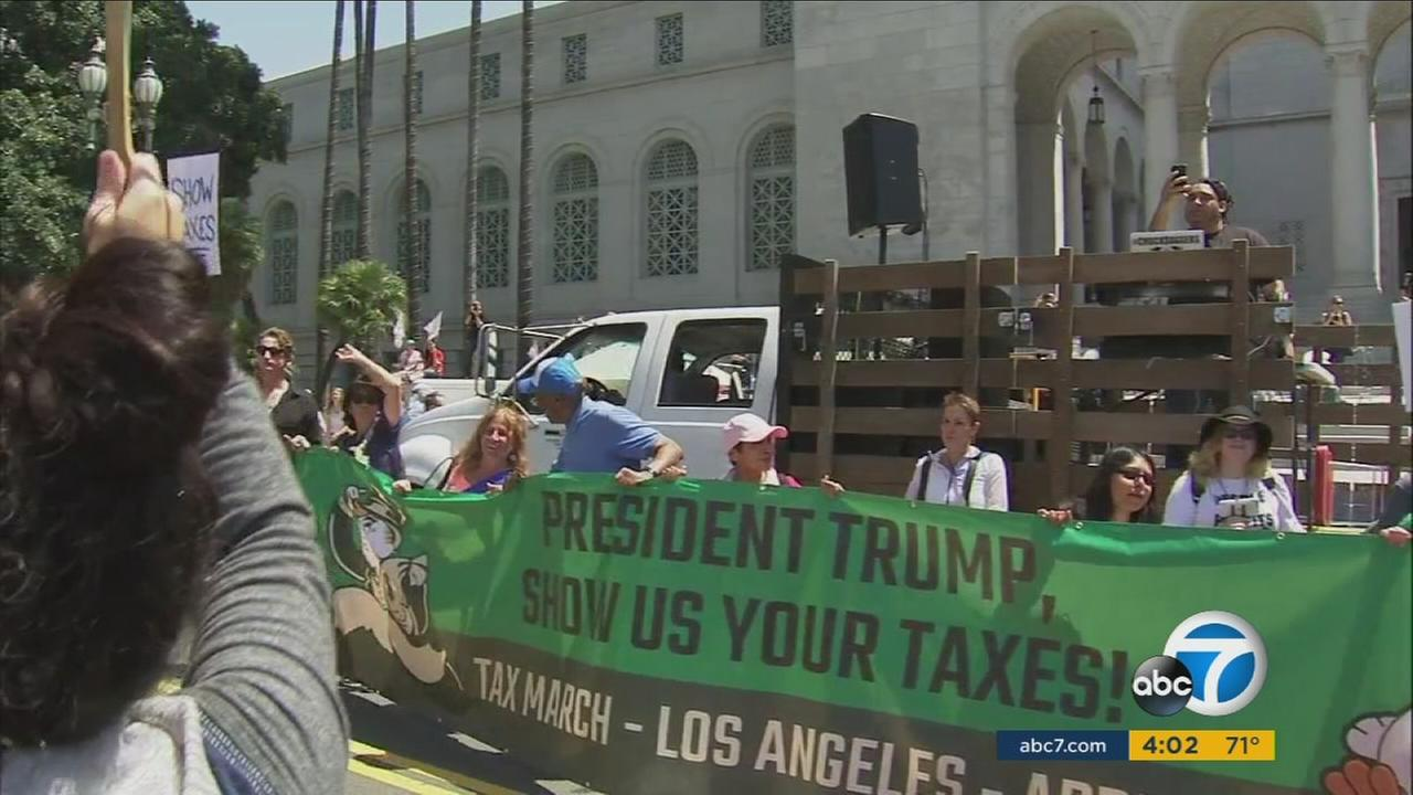 A group of protesters holding a sign demanding Trump to release his tax returns is shown in downtown Los Angeles on Saturday, April 15, 2017.