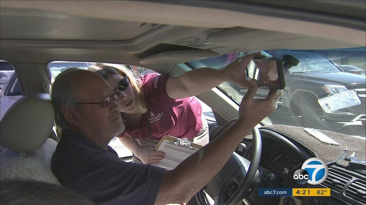 An occupational therapist helps out an older driver put in a panoramic rear view mirror to help with blind spots while driving in Downey.