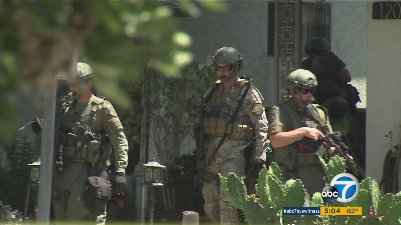 Authorities surrounded a neighborhood in Long Beach searching for a gunman who killed a woman at a motel on Friday, April 21, 2017.