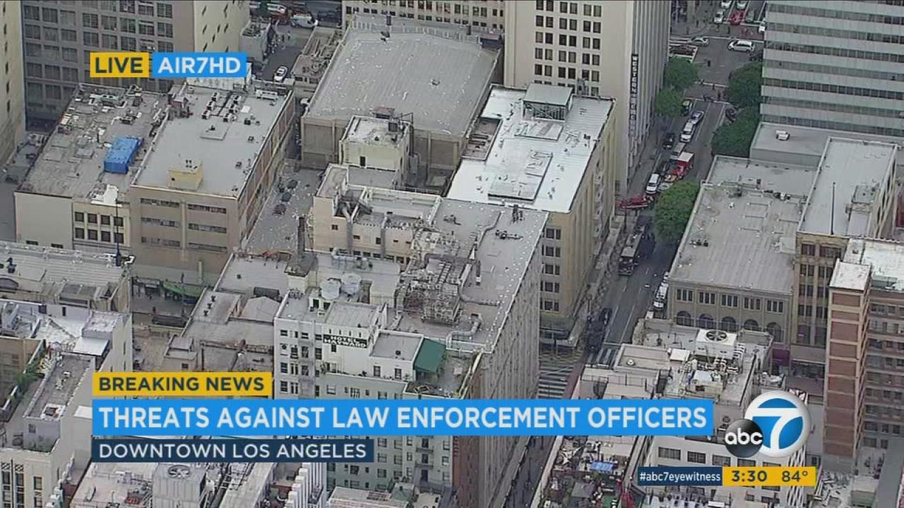 An armed man is threatening law enforcement after search warrants were served near 6th and Broadway in downtown Los Angeles, according to authorities.