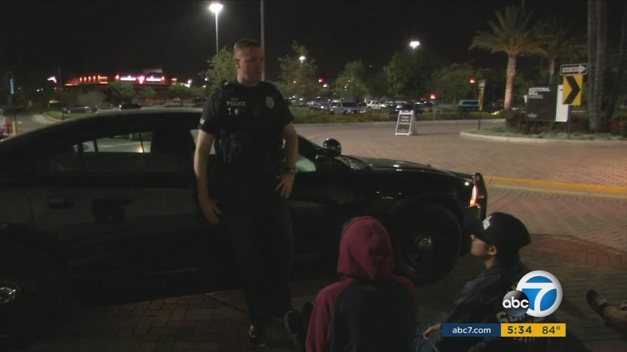 Teens talk to police during a curfew violation sweep in Orange County.