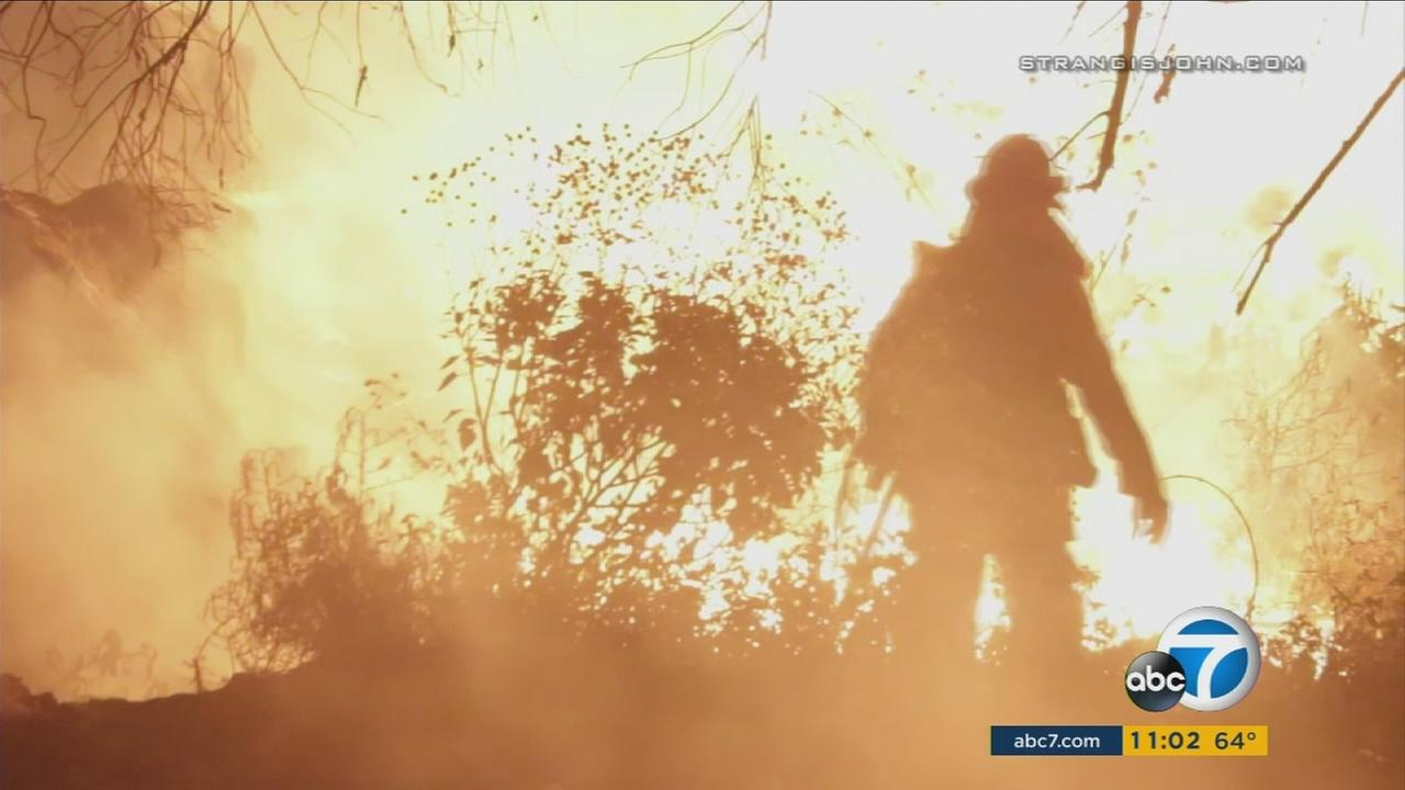 Silhouetted by flames, a firefighter battles a brush fire in Riverside County on Sunday, April 30, 2017.