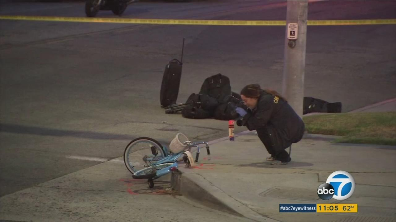 An investigator takes a photo of a bike ridden by a 13-year-old girl struck and killed by a bus in Redondo Beach on Friday, May 5, 2017.