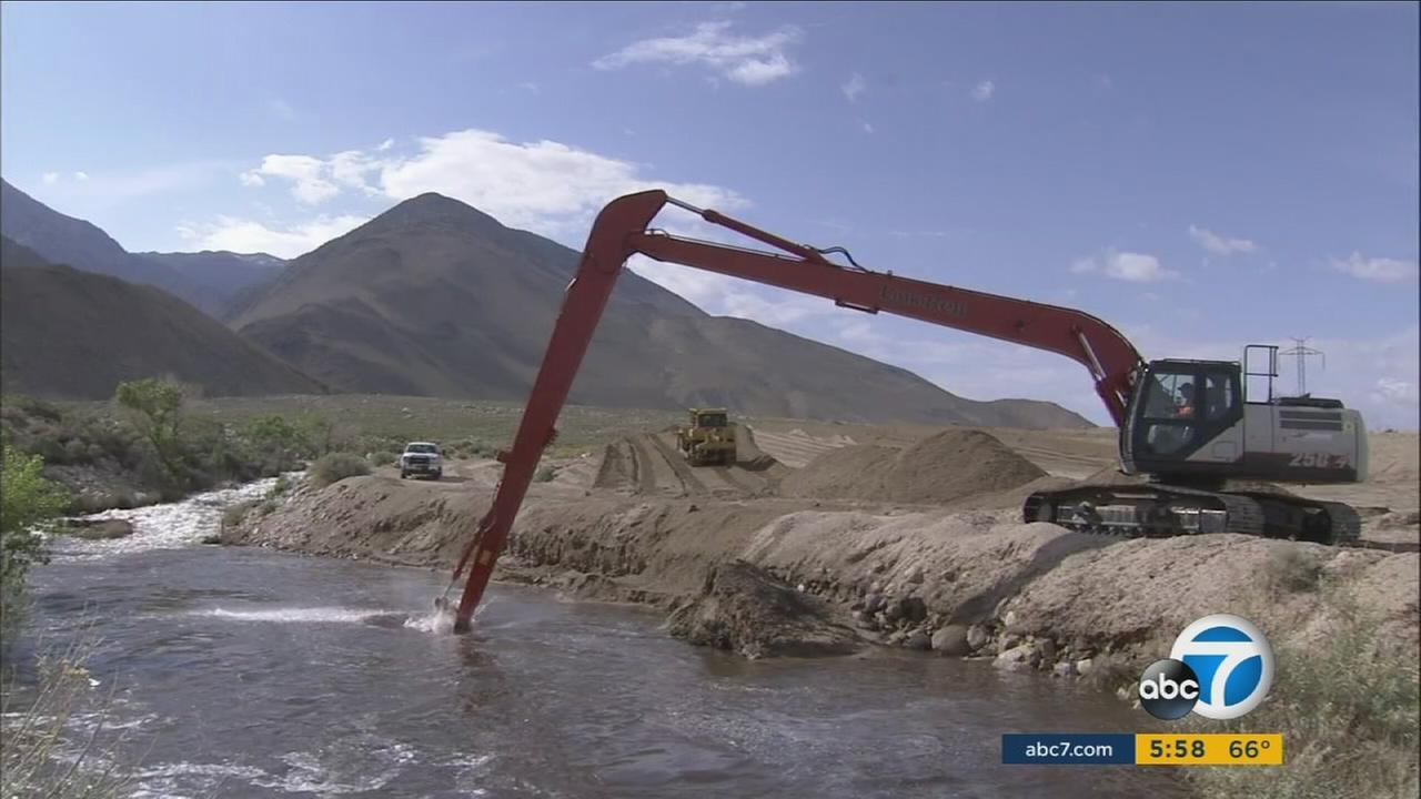 A LADWP construction machine removes gunk and debris from aqueducts and tributaries in Owens Valley.