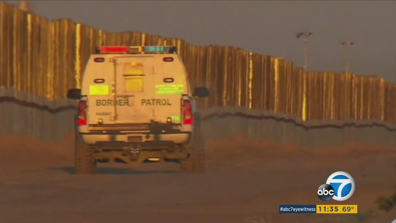 A file photo shows a border patrol vehicle at a border wall.
