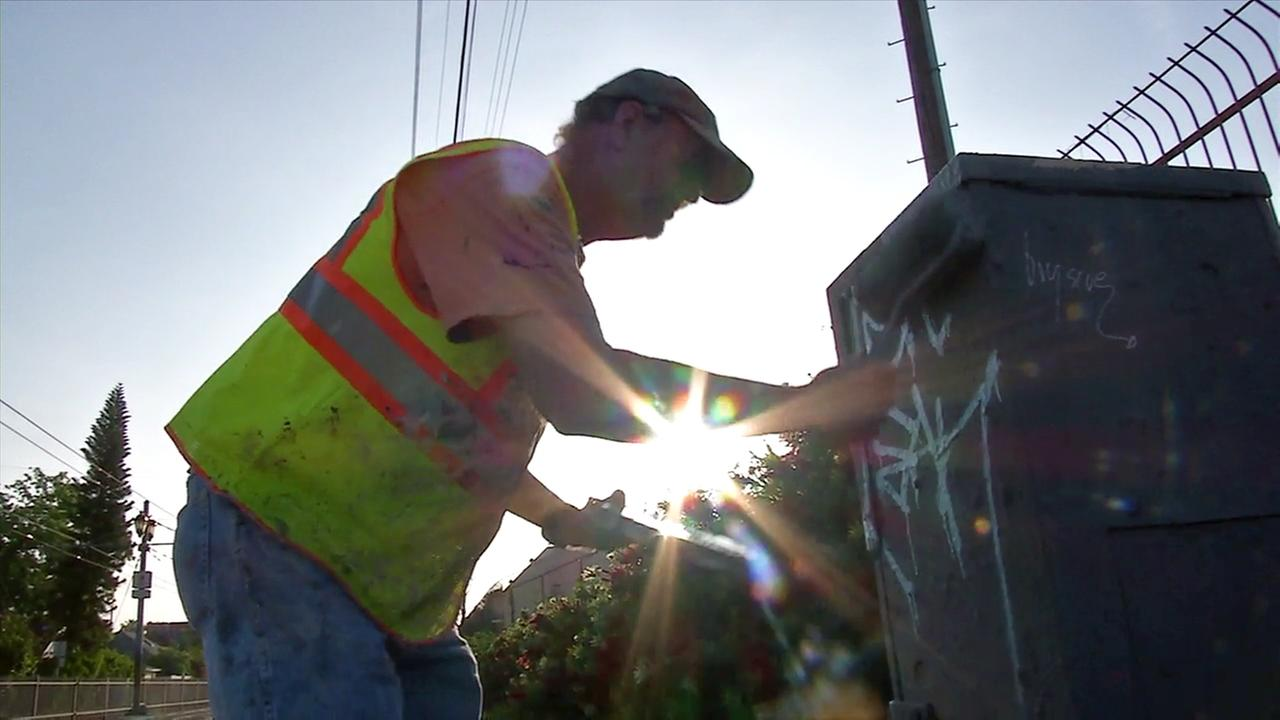 Larry Bender, a paint removal technician with Northeast Graffiti Busters, paints over graffiti in Los Angeles.