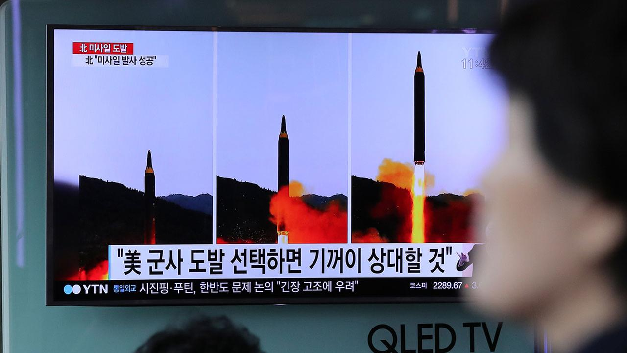A woman walks by a TV news program showing images of North Korean missile launch Monday, May 15, 2017.