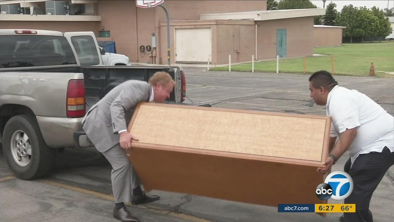 Two people lift a piece of furniture onto a truck as they prepare to donate it to those in need in Anaheim and surrounding communities.