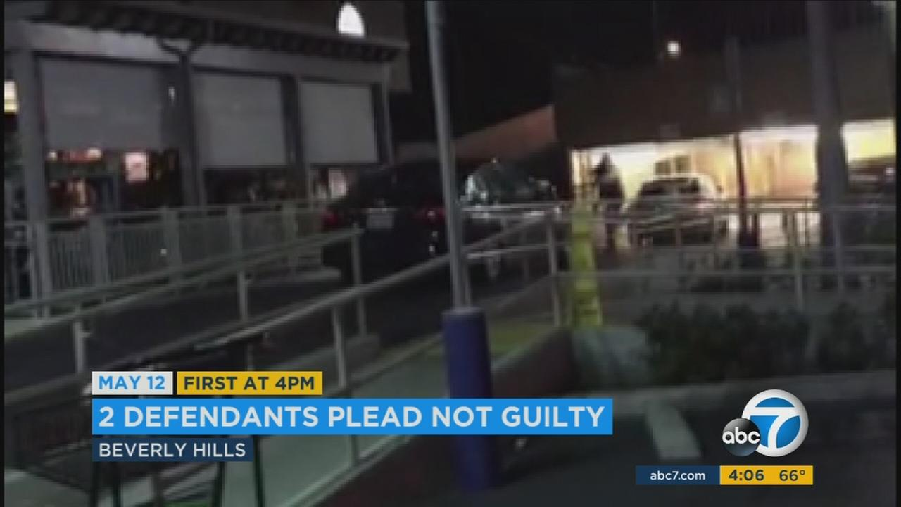 Two women have entered not guilty pleas to smashing a man with their car in a Beverly Hills parking lot, causing him to lose his leg below the knee.
