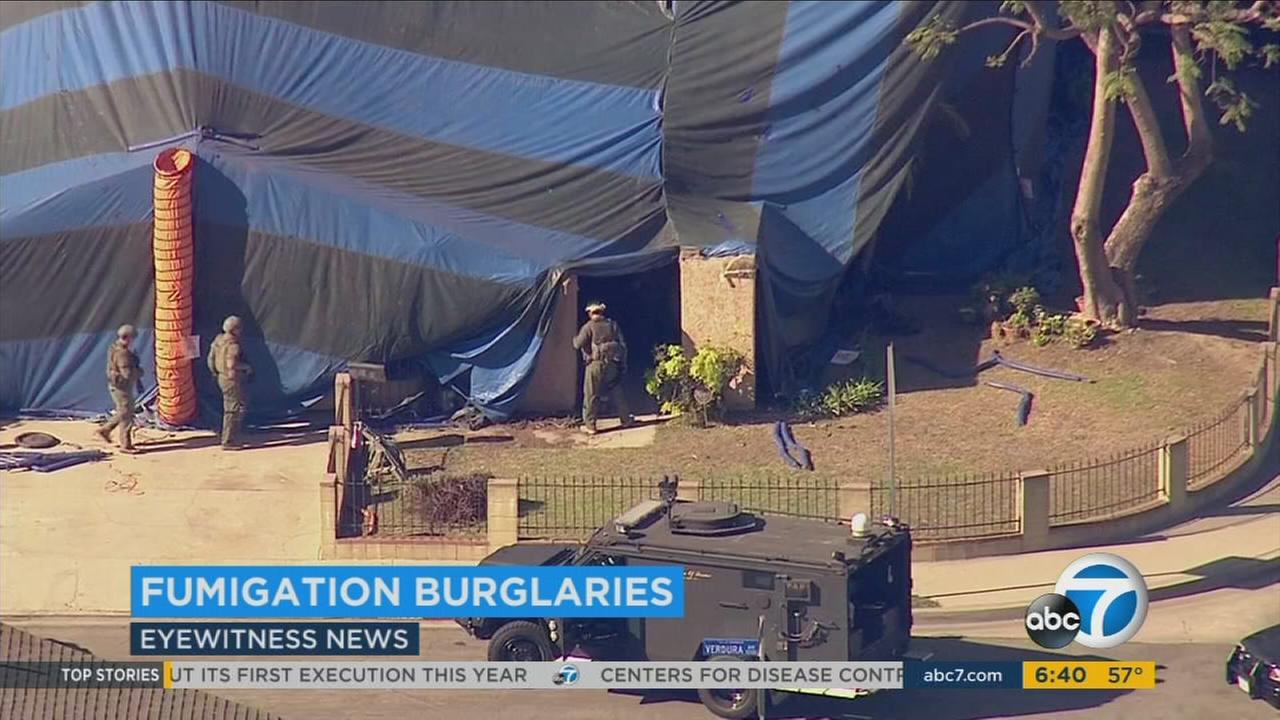 Law-enforcement personnel are seen entering a tented home in an undated file photo.