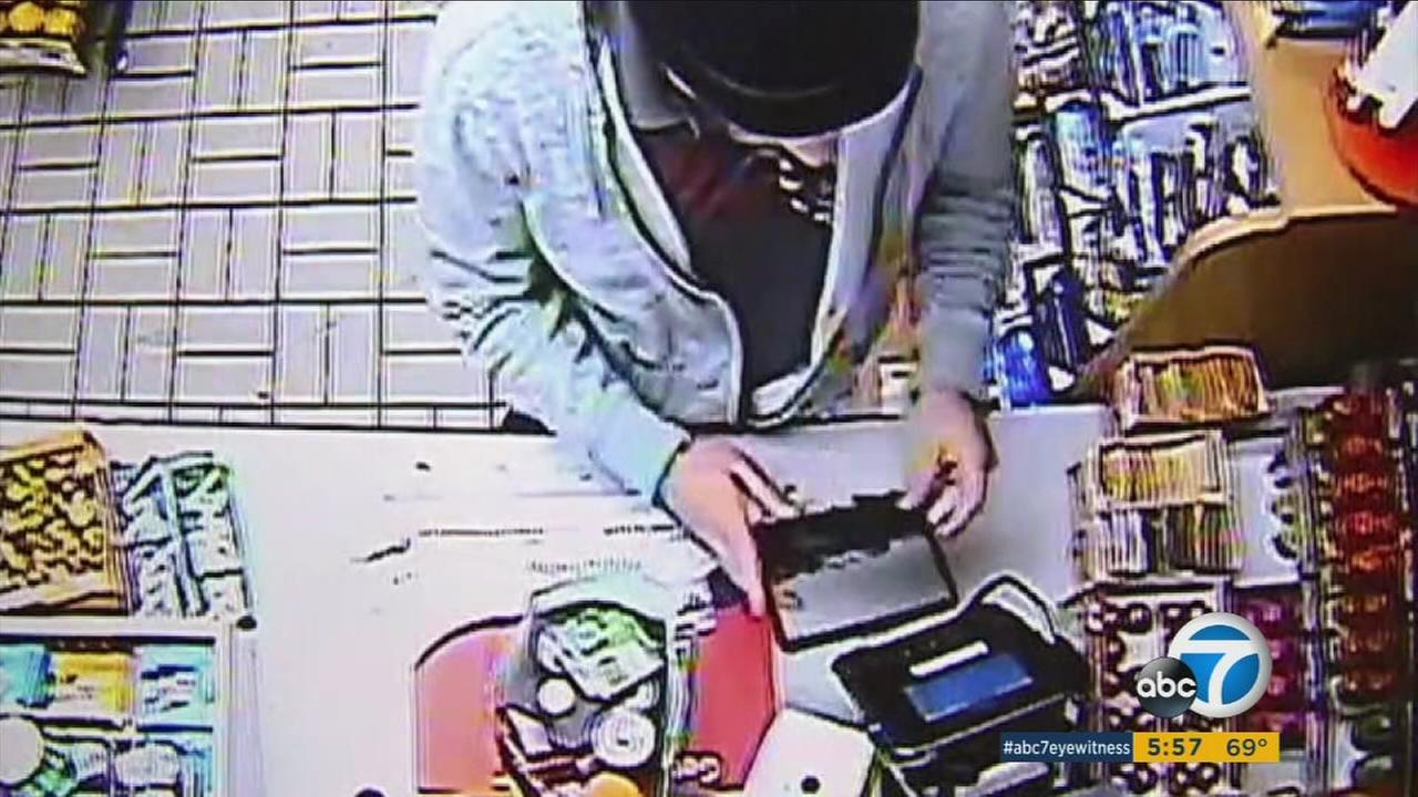 A suspected thief is shown placing a card skimmer on top of a card reader inside a West Los Angeles gas station.