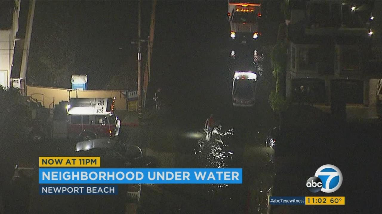 Footage from AIR7HD shows residents of a Newport Beach neighborhood wading through flooded streets.