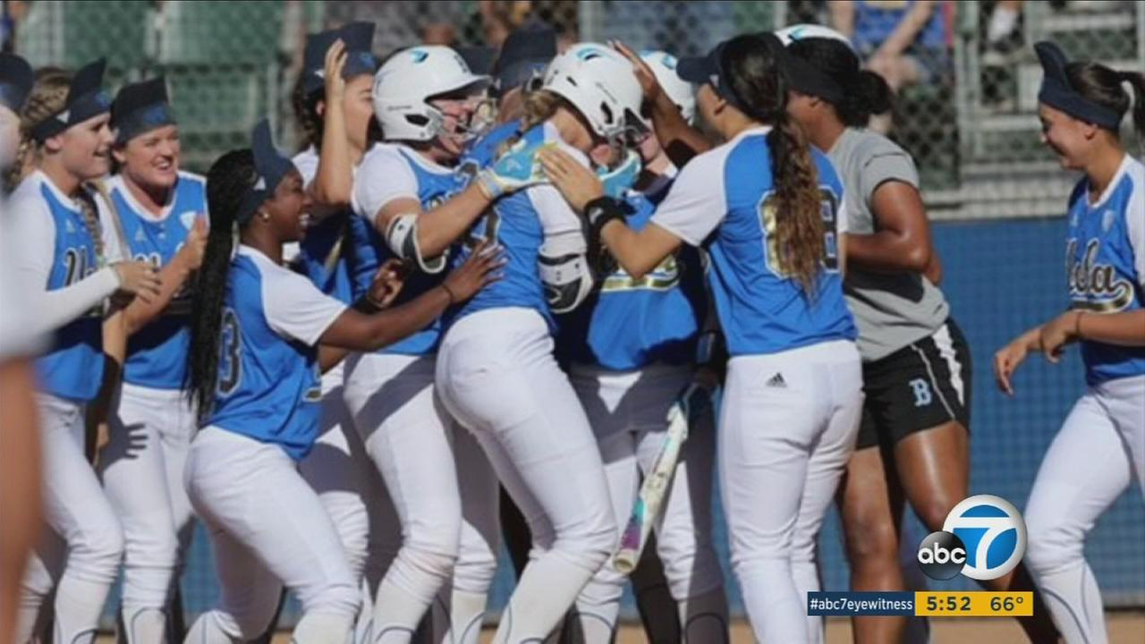 The UCLA Bruins womens softball team is shown celebrating during a game.