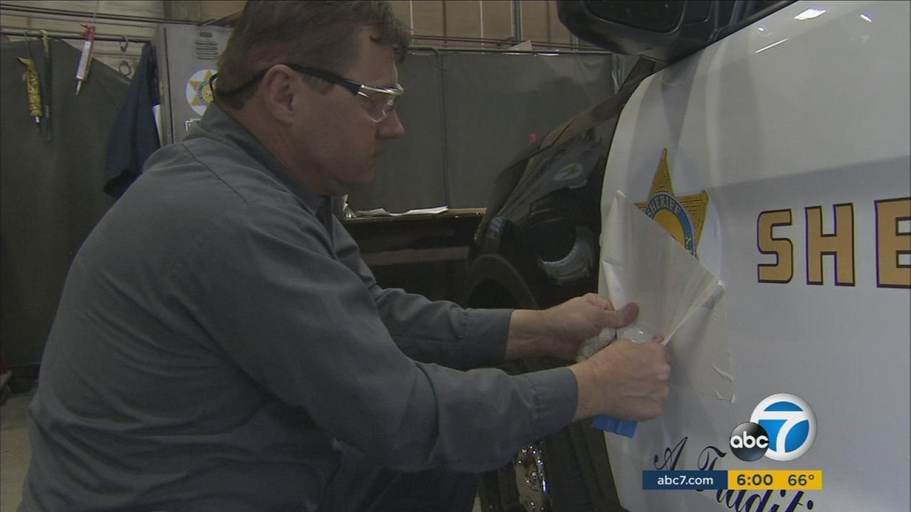 A man puts on a new decal along the side of a Los Angeles County Sheriffs Department patrol car.