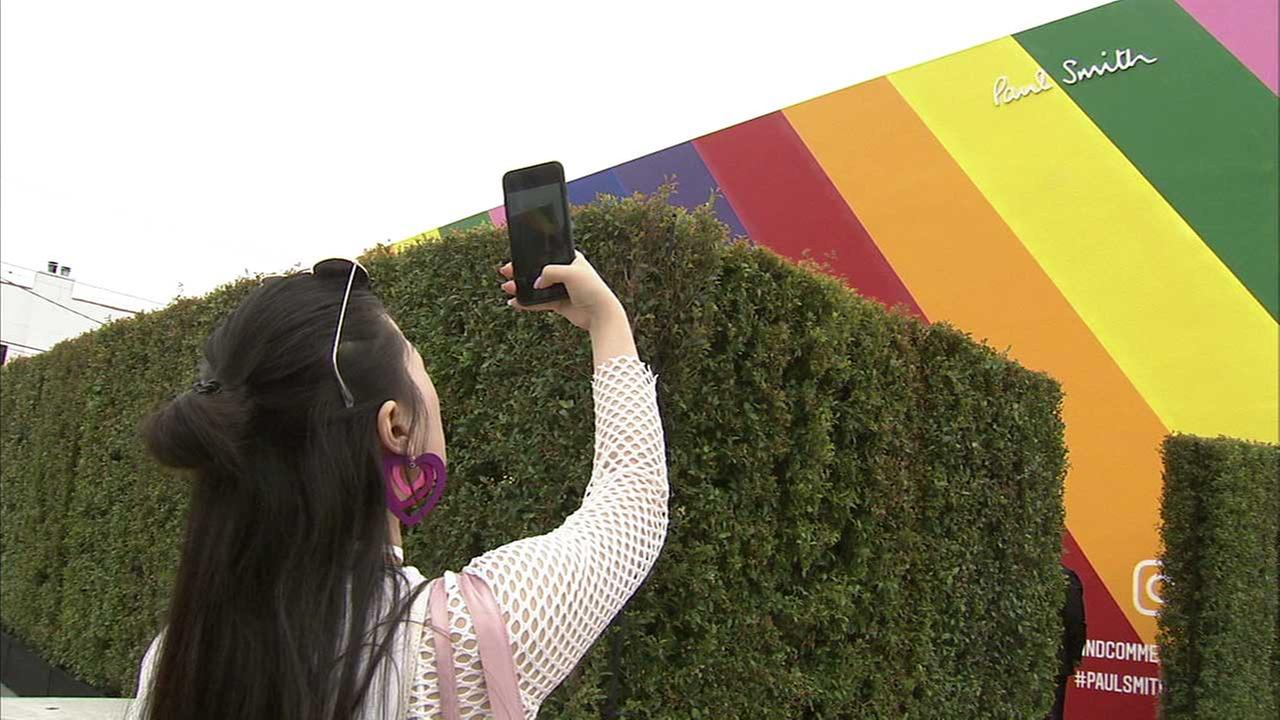 A woman takes a photo of the rainbow colored wall of the Paul Smith store on Melrose Avenue in Los Angeles on Wednesday, May 31, 2017.