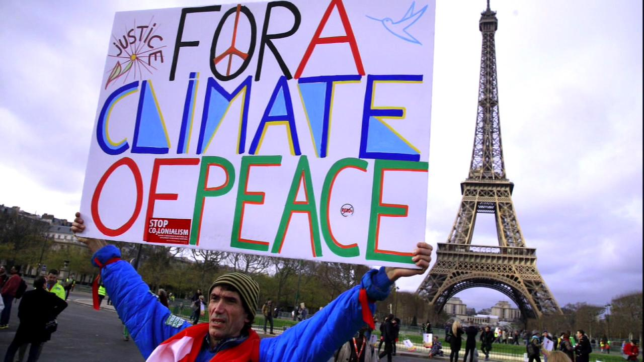 An undated photo of a protester in front of the Eiffel Tower, speaking out against President Donald Trump leaving the Paris climate accord.