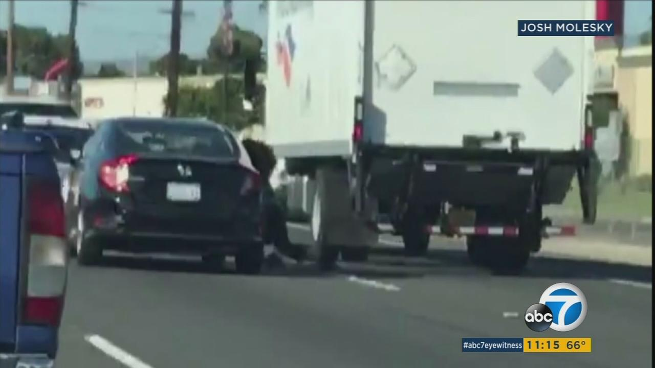 In a suspected road rage incident in Santa Ana, a witness caught a woman holding onto the side of a car as it travels through lanes on the 55 Freeway.