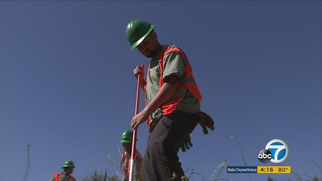 Oscar Ayala, 18, is shown doing work while with a clean and green program in Los Angeles.