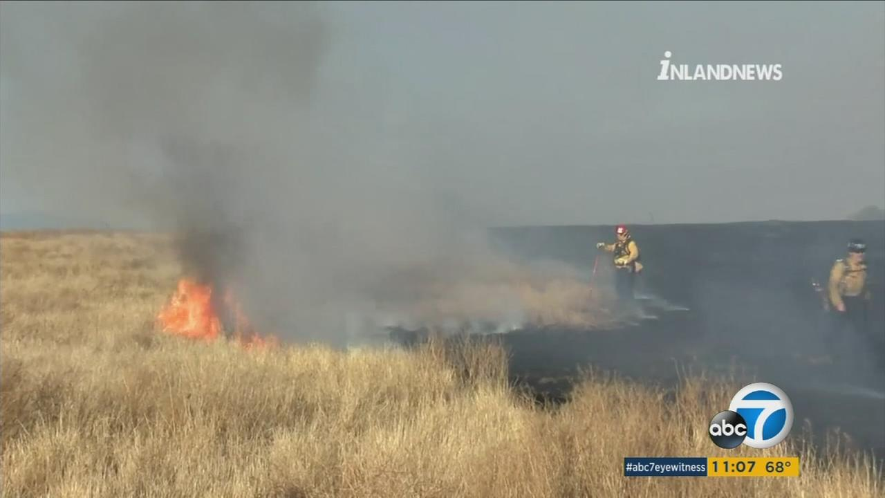 A small brush fire in Bloomington threatened homes in the area amid scorching heat in the Southland.